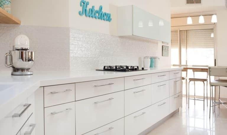 מטבח מודרני עמוס בארונות לבנים